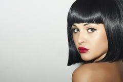 Härlig brunettflicka. Sunt svart hår. guppar frisyr. röda kanter. skönhetkvinna royaltyfria foton