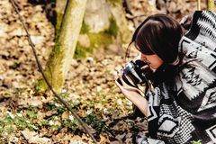 Härlig brunettkvinna i bohoponchon som tar foto på motsvarighet royaltyfria bilder