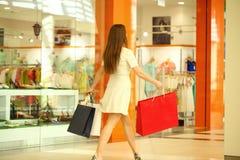 Härlig brunettkvinna i den vita klänningen med några shoppa påsar i gallerian fotografering för bildbyråer