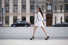 Härlig brunettkvinna i den vita klänningen som går på gatan arkivfoto