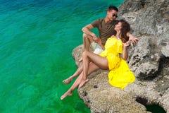 Härlig brunettkvinna i en gul klänning och hennes make på th royaltyfri bild