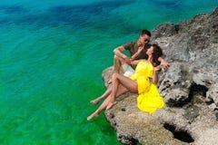 Härlig brunettkvinna i en gul klänning och hennes make på th fotografering för bildbyråer