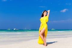 Härlig brunettkvinna i en gul klänning på det tropiska havet c royaltyfria foton