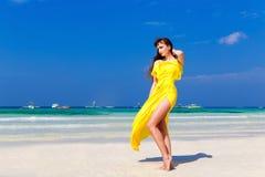 Härlig brunettkvinna i en gul klänning på det tropiska havet c fotografering för bildbyråer