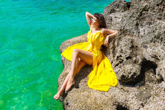 Härlig brunettkvinna i en gul klänning på det tropiska havet c royaltyfri fotografi