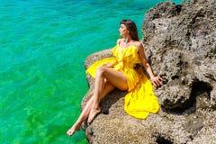 Härlig brunettkvinna i en gul klänning på det tropiska havet c arkivbild