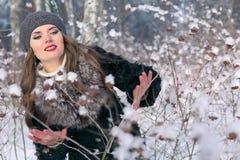 Härlig brunettkvinna i ett basker- och pälslag som poserar och ler på bakgrunden av den snöig skogen Royaltyfri Bild