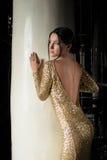 Härlig brunettkvinna i guld- klänning Arkivfoton