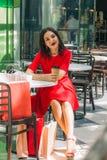Härlig brunettkvinna i röd klänning som dricker kaffe i en coffee shop arkivbilder