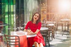 Härlig brunettkvinna i röd klänning som dricker kaffe i en coffee shop arkivfoton