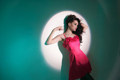 Härlig brunettkvinna i stråle av strålkastaren Arkivfoto
