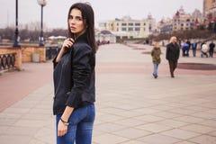 Härlig brunettkvinna i svart läderomslag som går på Royaltyfri Fotografi