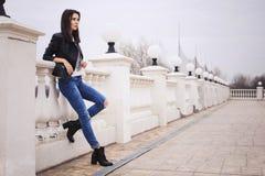 Härlig brunettkvinna i svart läderomslag som går på Royaltyfri Bild