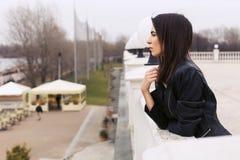 Härlig brunettkvinna i svart läderomslag som går på Arkivbild