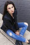 Härlig brunettkvinna i svart sammanträde för läderomslag på Arkivbilder