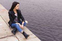 Härlig brunettkvinna i svart sammanträde för läderomslag på Arkivfoto