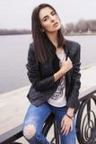 Härlig brunettkvinna i svart sammanträde för läderomslag på Royaltyfri Foto