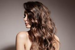 Härlig brunettkvinna. Lockigt långt hår. Arkivfoton
