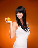 Härlig brunettkvinna med apelsinen på orange bakgrund Fotografering för Bildbyråer