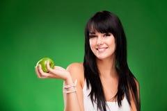 Härlig brunettkvinna med det gröna äpplet på gräsplan Royaltyfri Foto