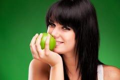 Härlig brunettkvinna med det gröna äpplet på grön bakgrund Arkivbild