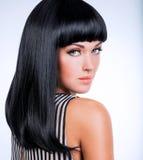 Härlig brunettkvinna med långt svart rakt hår Arkivbild