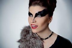 Härlig brunettkvinna med makeup i stilen av kvinnakatter royaltyfria bilder