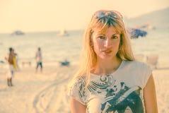 Härlig brunettkvinna med solglasögon på huvudet på stranden royaltyfri fotografi