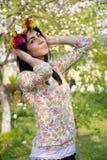 Härlig brunettkvinna med trädgården för blommakrans på våren Arkivfoton