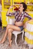 Härlig brunettkvinna på en 7th månadhavandeskap i plädskjorta Arkivbilder