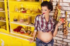Härlig brunettkvinna på en 7th månadhavandeskap i plädskjorta Arkivbild