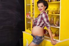 Härlig brunettkvinna på en 7th månadhavandeskap i plädskjorta Royaltyfria Bilder