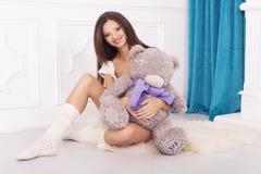 Härlig brunettkvinna på en 7th månadhavandeskap i vit under Royaltyfri Fotografi