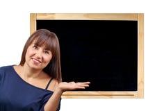 Härlig brunettkvinna som framlägger den tomma svart tavlan för svart tavla Royaltyfria Foton
