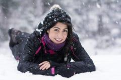 Härlig brunettkvinna som ligger på snön som tycker om vintersnön Arkivfoto