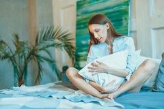 Härlig brunettkvinna som sträcker i säng efter vak upp Royaltyfria Bilder