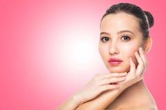 Härlig brunettkvinna Spa med ren hud, naturlig makeup på rosa bakgrund med kopieringsutrymme arkivbild