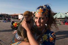 Härlig brunettkvinnastående med en sjalett och en apa i hennes armar arkivbilder