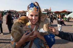 Härlig brunettkvinnastående med en sjalett och två apor i hennes armar arkivfoto