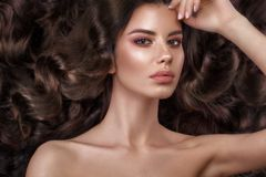 Härlig brunettmodell: krullning, klassisk makeup och fulla kanter Skönhetframsidan fotografering för bildbyråer