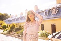 Härlig brunettmodell som poserar på gatan i strålar av solen Fotografering för Bildbyråer