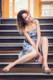 Härlig brunn-ansad kvinna i en blå klänning som sitter på trappan Hon är le och se kameran arkivbilder