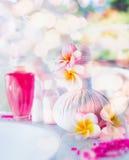 Härlig brunnsort- och wellnessinställning med blommor, massagehjälpmedel och lotion, främre sikt Sund livsstil arkivbild