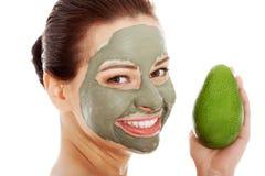 Härlig brunnsortkvinna i ansikts- maskering och avokado. Arkivbilder