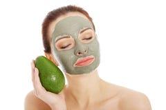 Härlig brunnsortkvinna i ansikts- maskering och avokado Royaltyfri Bild