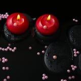 Härlig brunnsortstilleben av stearinljus, zenstenar med droppar Arkivfoto