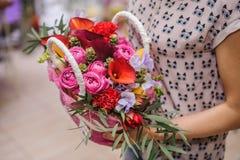 Härlig bukett av den ljusa blommakorgen i händer Fotografering för Bildbyråer