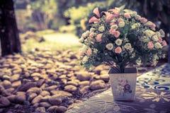 Härlig bukett av konstgjorda blommor i en keramisk vas på medeltal Arkivbild