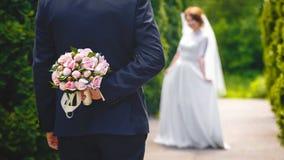 Härlig bukett av nya blommor i händer av brudgummen Royaltyfri Bild