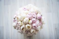 Härlig bukett av rosa och vita pioner i en ask på golvet övre sikt royaltyfria bilder